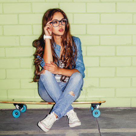 sexual activities: young beautiful long-haired brunette woman sit on wooden longboard skateboard and touch her glasses near the green brick wall