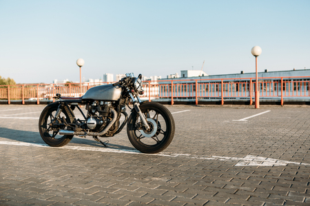 urban environments: Silver vintage custom motorbike motorcycle cafe racer on empty rooftop parking lot at city center surrounded by urban environments midtown buildings. Hipster style, student dream, wild lifestyle.