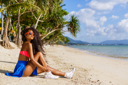 Outdoor lifestyle portrait of black beautiful teenage girl in bright outfit. Young hipster woman untying laces in her white  sneakers. Sunny hot summer day at tropical seashore with palms. Фото со стока