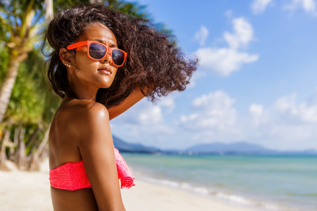 Outdoor lifestyle portrait of black beautiful teenage girl in pink bra and sunglasses. Young hipster woman play with her hair. She is happy. Sunny hot summer day at tropical sea beach with palms.