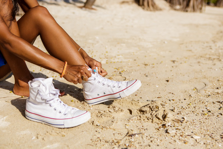 converse: Outdoor lifestyle close-up of the legs of black beautiful teenage girl. Young hipster woman tying laces in her white converse sneakers. Sunny hot summer day at tropical seashore.