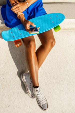 mixed race woman: Outdoor lifestyle portrait of black young lady in bright outfit. Hipster girl sitting at skate park with blue penny shortboard skateboard and texting on the smartphone phone. Swag, fashion. Sunny day.
