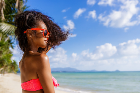 pink bra: Outdoor lifestyle portrait of black beautiful teenage girl in pink bra and sunglasses. Young hipster woman play with her hair. She is happy. Sunny hot summer day at tropical ocean beach with palms.