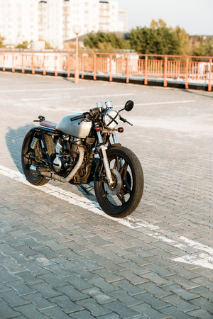 urban environments: Front view of silver vintage custom motorbike motorcycle caferacer on empty rooftop parking lot surrounded by urban environments midtown buildings. Hipster style, student dream, wild lifestyle.