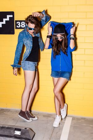going crazy: Lifestyle portrait of two beautiful best friends hipster girls wearing stylish bright outfits, denim shorts and sunglasses going crazy and having great time. Standing together near yellow brick wall enjoying day off and have fun. Stock Photo