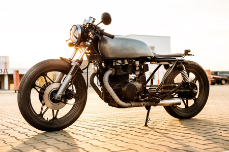 urban environments: One silver vintage custom motorbike caferacer motorcycle on empty rooftop parking lot surrounded by urban environments midtown buildings during sunset. Hipster lifestyle, student dream. Stock Photo