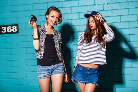 Lifestyle portrait of two beautiful best friends hipster woman wearing stylish bright outfits and denim shorts going crazy and having great time. Standing together near blue brick wall with photo camera and have fun while pose for selfie self portrait. Yo
