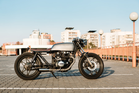 urban environments: Silver vintage custom motorcycle motorbike caferacer on empty rooftop parking lot at city center surrounded by urban environments midtown buildings. Hipster style, student dream, wild lifestyle. Stock Photo