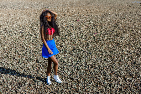 pink bra: Outdoor lifestyle portrait of black sexy lady in blue mini skirt, pink bra and sunglasses. Tanned hipster girl with long healthy curved hairs posing at stones beach. Sunny hot summer holiday day.