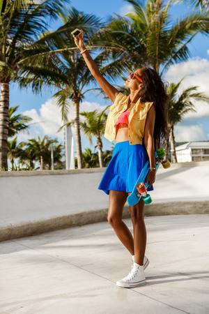 mannequin africain: mode de vie en plein air portrait noir jeune femme en tenue brillante. fille Hipster au skate park avec le bleu penny longboard planche à roulettes de prendre un selfie autoportrait. Ensoleillé chaude journée d'été. Swag, la mode.