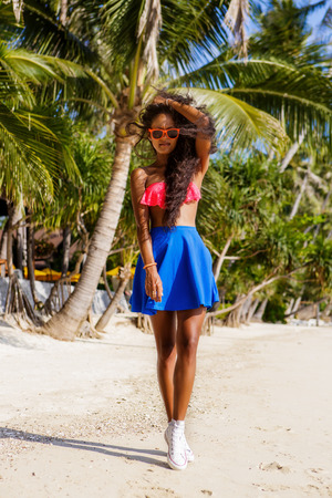 converse: Outdoor lifestyle portrait of black beautiful teenage girl in blue skirt and white converse sneakers. Young hipster woman correct her curly hair. Sunny hot summer day at tropical beach with palms.