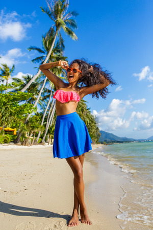 pink bra: Outdoor lifestyle portrait of black teenage girl in pink bra and blue skirt. Young hipster woman correct her pink sunglasses. Sunny hot summer day at tropical beach with palms. Happy lady life.