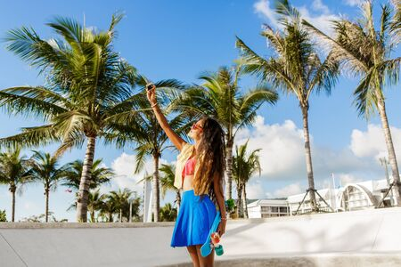 hot day: Outdoor lifestyle portrait of smiling black young woman in bright outfit. Hipster girl with penny skateboard taking selfie self portrait on her smartphone digital camera. Sunny hot day. Swag, fashion. Stock Photo