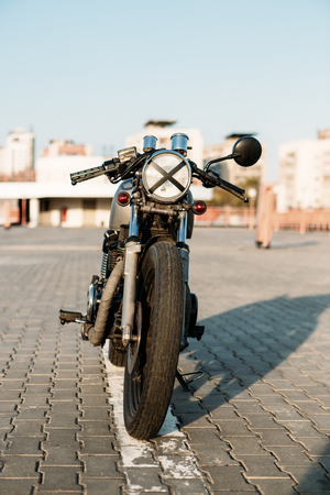 urban environments: Front view of silver vintage custom motorcycle motorbike cafe racer on empty rooftop parking lot surrounded by urban environments midtown buildings. Hipster style, student dream, wild lifestyle.