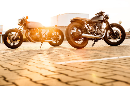Two vintage custom motorbike caferacers motorcycle looking in opposite directions on empty rooftop parking lot with backlight sun during sunset. Confrontation of urban styles. Hipster lifestyle. Фото со стока