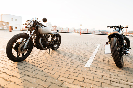 urban environments: Two vintage custom motorcycles cafe racer motorbike on empty rooftop parking lot surrounded by urban environments midtown buildings during sunset. Hipster lifestyle, student dream.