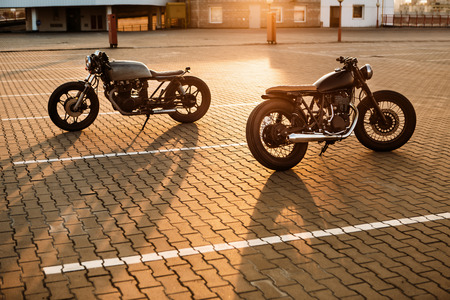Two vintage custom motorbikes cafe racer silver and black motorcycle directed in opposite directions on empty rooftop parking lot during sunset. Hipster lifestyle. Confrontation of urban styles.