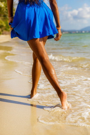 afro caribbean ethnicity: Outdoor lifestyle close-up of long beautiful legs of a sporty black teenage girl at tropical seashore. Closeup detail of female feet, water splash and golden sand. Young hipster, sunny hot summer day.
