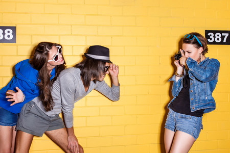 cute teen girl: Образ жизни портрет красивых лучший друг хипстеров, носить стильный яркий одежду и солнцезащитные очки и имеющие большое время. Одна дама принимая фотографии мальчика с его женой перед желтой кирпичной стеной.