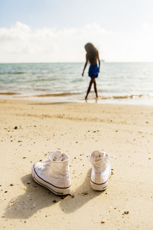 converse: Outdoor lifestyle close-up of the white converse sneakers at tropical seashore. Silhouette of a black beautiful teenage girl with long legs on a background. Young hipster woman, sunny hot summer day. Stock Photo