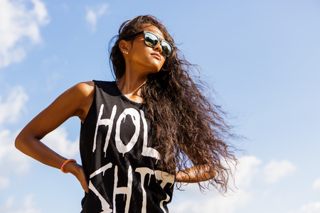 hair curly: Outdoor portrait of a beautiful teenage black girl with curly hair in dark sunglasses and t-shirt. Lifestyle portrait with blue sky at background. Freedom and happiness. Stock Photo