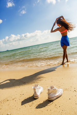 converse: Outdoor lifestyle close-up of white converse sneakers at tropical seashore. Silhouette of sporty black beautiful teenage girl with long legs on a background. Young hipster woman, sunny hot summer day. Stock Photo