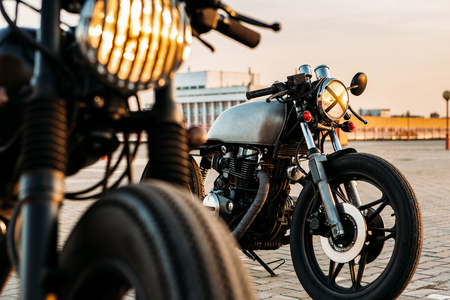 outdoor cafe: Vintage custom motorcycle cafe racer motorbike with lamp lights turned on. One with grill headlight another with tape cross over optic on empty rooftop parking lot during sunset. Hipster lifestyle. Stock Photo