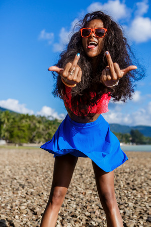 Outdoor lifestyle close-up of a black sexy lady in blue skirt, pink bra and sunglasses show tongue and two hands with middle finger, fuck you off sign. Hipster girl at stones beach. Sunny day. Swag. Stock Photo