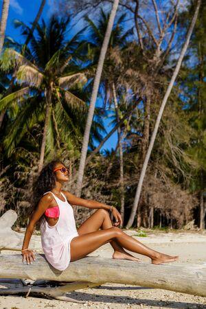 chicas guapas: retrato vida al aire libre de la se�ora atractiva en sujetador negro rosa y camiseta blanca. chica inconformista bronceada se sienta en la palmera seca. D�a soleado vacaciones de verano calientes en la playa tropical con palmeras. la moda bot�n. Foto de archivo