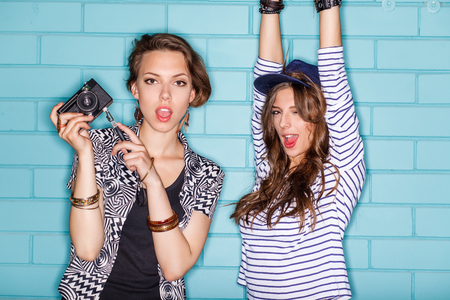 going crazy: Lifestyle portrait of two beautiful best friends hipster girls wearing stylish bright outfits going crazy and having great time. Standing together near blue brick wall with photo camera and have fun while taking selfie self portrait of each other. Young a