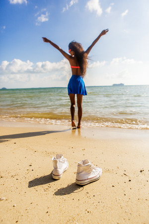 afro caribbean ethnicity: Outdoor lifestyle close-up of a white e sneakers at tropical seashore. Silhouette of a black beautiful teenage girl with long legs on a background. Young hipster woman, sunny summer day.