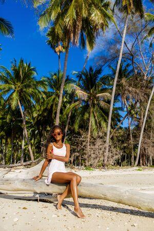 maillot de bain fille: mode de vie en plein air portrait noir dame sexy en soutien-gorge rose et t-shirt blanc. Bronzé hippie fille posant sur palmier sec. Journée ensoleillée des vacances d'été chaud à la plage tropicale de l'océan avec des palmiers. la mode Swag.