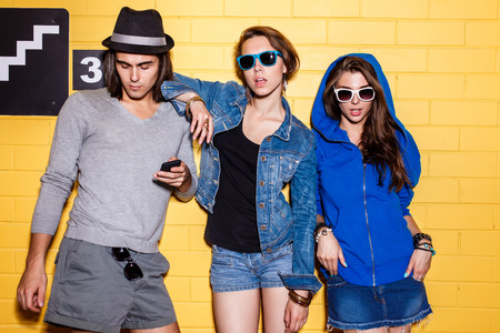 Lifestyle portrait of beautiful best friend hipsters wearing stylish bright outfits and sunglasses and having great time. Girls are looking to the camera in front of yellow brick wall enjoying day off and have fun. Boy with smartphone cellphone. Stock Photo