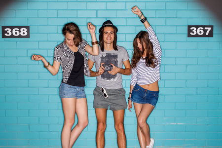 Lifestyle portrait of beautiful best friend hipsters wearing stylish bright outfits and having great time. Poses for the camera in front of blue brick wall enjoying day off and have fun. Two beautiful dancing girls and smiling boy in hat with photo camera photo