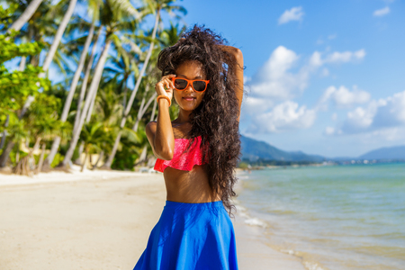 hot pink: Outdoor lifestyle portrait of black sexy lady in pink bra and blue skirt. Tanned hipster woman smile and correct her bright sunglasses. Sunny hot summer day at tropical beach with palms. Swag.