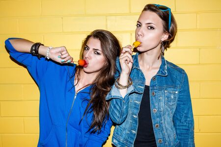 Lifestyle portrait of two beautiful best friends hipster girls wearing stylish bright outfits and having great time. Standing together near yellow brick wall enjoying day off, have fun and eating sweet ice-cream. photo
