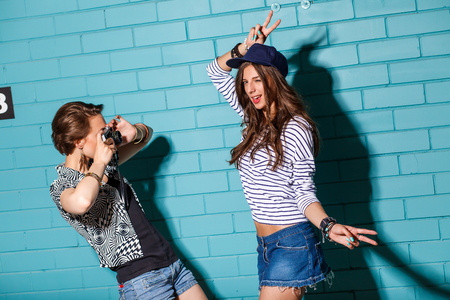 Lifestyle portrait of two beautiful best friends hipster girls wearing stylish bright outfits and denim shorts going crazy and having great time. Standing together near blue brick wall with photo camera and have fun while one taking picture of her friend  photo