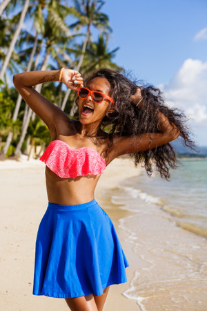pink bra: Outdoor lifestyle portrait of black teenage girl in pink bra and blue skirt. Young hipster woman correct her pink sunglasses and happily scream. Sunny hot summer day at tropical beach with palms.