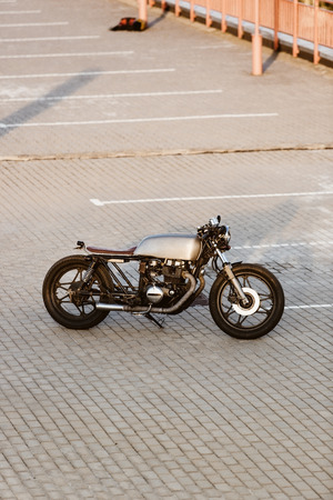 urban environments: One silver vintage custom motorbike motorcycle cafe racer on empty rooftop parking lot at city center surrounded by urban environments midtown buildings. Hipster style, student dream, wild lifestyle.
