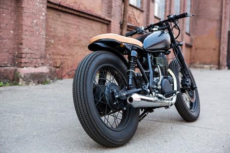 Schwarzer Vintage benutzerdefinierte motorrad caferacer vor Mauer. Rückansicht. Standard-Bild