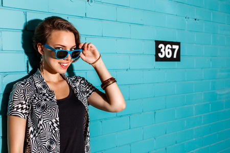 Young beautiful sexy lady in modern jacket and black t-shirt playing with her sunglasses while smiling to the camera in front of blue brick wall. photo
