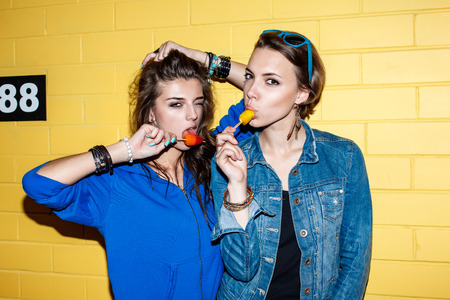 Lifestyle portrait of two beautiful best friend hipster lady wearing stylish bright outfits and having great time. Standing together near yellow brick wall enjoying day off, have fun and eating sweet cold ice-cream. photo