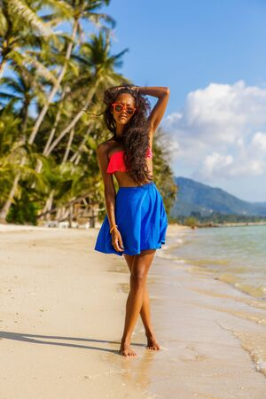 afro caribbean ethnicity: Outdoor lifestyle portrait of black teenage girl in pink bra and blue skirt. Young hipster woman with crossed beautiful legs correct her curly hair. Sunny hot summer day at tropical beach with palms.