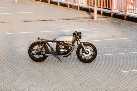 urban environments: One silver vintage custom motorbike caferacer motorcycle on empty rooftop parking lot at city center surrounded by urban environments midtown buildings. Hipster style, student dream, wild lifestyle.