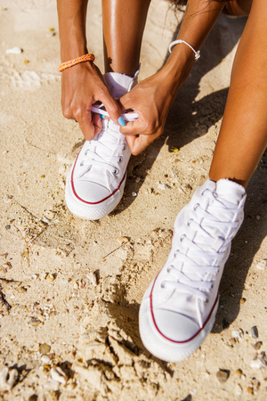 afro caribbean ethnicity: Outdoor lifestyle close-up of the legs of black beautiful teenage girl. Young hipster woman untying laces in her white  sneakers. Sunny hot summer day at tropical seashore.