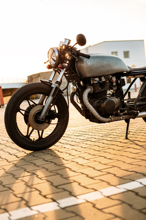 urban environments: One silver vintage custom motorbike cafe racer motorcycle at empty rooftop parking lot surrounded by urban environments midtown buildings during sunset. Hipster lifestyle, student dream. Stock Photo