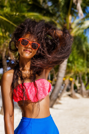 pink bra: Outdoor lifestyle close-up of black beautiful teenage girl in pink bra and sunglasses. Young hipster woman play with her hair. She is happy. Sunny hot summer day at tropical ocean beach with palms. Stock Photo