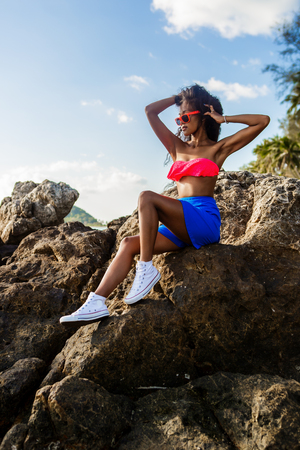 pink bra: Outdoor lifestyle portrait of a black sexy lady in blue skirt, white converse sneakers, pink bra and sunglasses. Hipster girl sitting at big rock at stone beach. Sunny summer holiday. Swag, fashion. Stock Photo