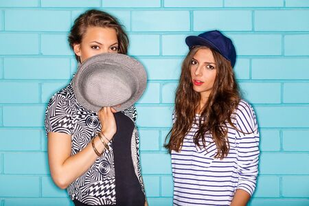 Lifestyle portrait of two beautiful best friends hipster lady wearing stylish bright outfits, denim shorts going crazy and having great time. Standing together near blue brick wall enjoying day off and have fun. photo
