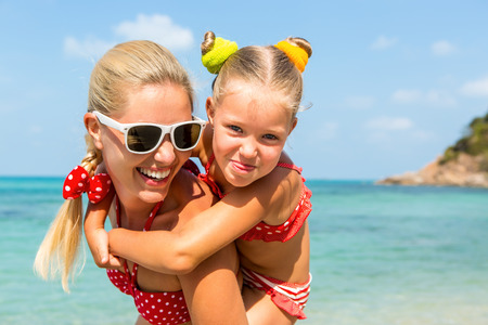 mammy: Beautiful mom sunglasses with cute little daughter on her back. Two in red bikini. Woman and little girl smile and looking to camera. Happy family on the sea shore. Happy mothers day.
